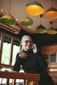 Senior woman making a phone call at coffee shop