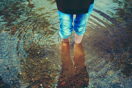 Woman feet in cold water