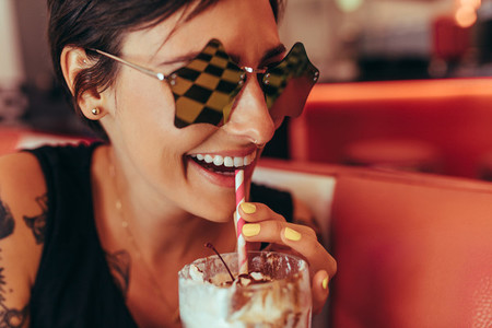 Close up of a woman drinking milkshake with a straw at a diner
