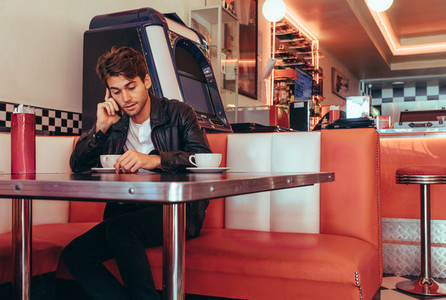 Man talking over mobile phone sitting at a restaurant
