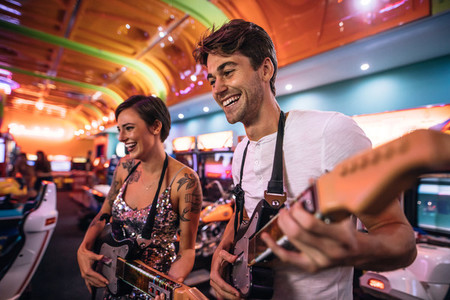 Happy couple playing a guitar arcade game