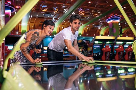 Couple enjoying a game of air hockey at a gaming arcade