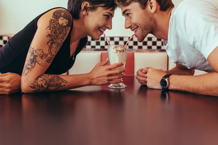 Man and woman sharing milk shake from one glass using straws
