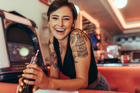 Smiling woman at a diner drinking soft drink