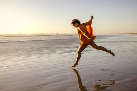 Woman having fun running on the sea shore