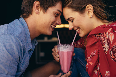 Romantic couple sharing a milkshake
