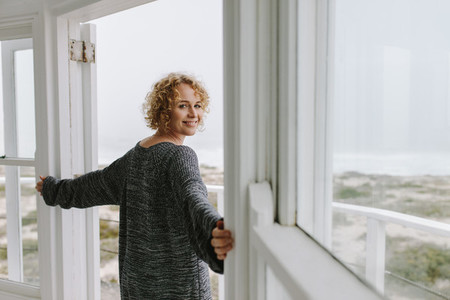 Side view of a woman standing at the door looking at the beach