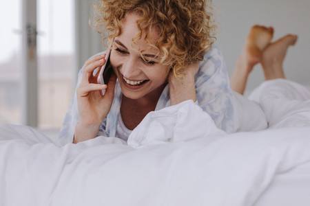 Smiling woman lying on bed talking on mobile phone