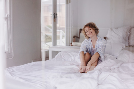 Smiling woman sitting on bed with eyes closed