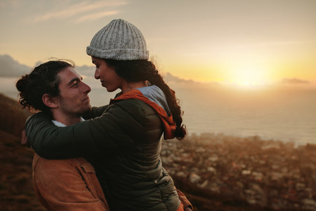 Affectionate couple on mountain at sunset