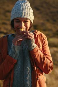 Woman in winter wear smelling a flower on mountain