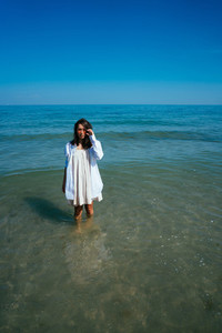 The girl is standing in the sea by the shore