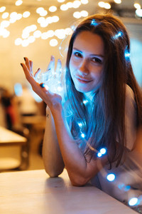 Woman holding glowing christmas garland in hands
