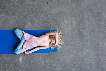 Young slim blond woman making yoga exercises