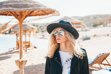 young woman in straw hat and sunglasses on beach