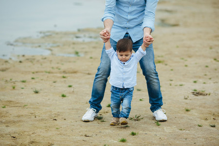 Dad holding infant sons hands