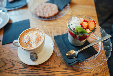 Cappuccino with spoon in cup and dessert