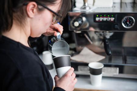 Female barista makes coffee