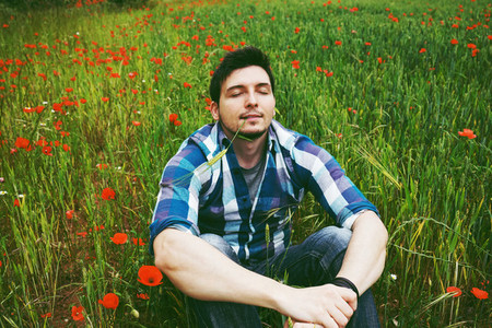 Young relaxed man in a field