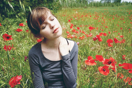 Young woman in a poppy field