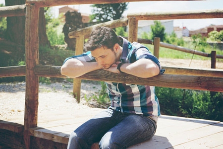 Young man sitting in a bridge
