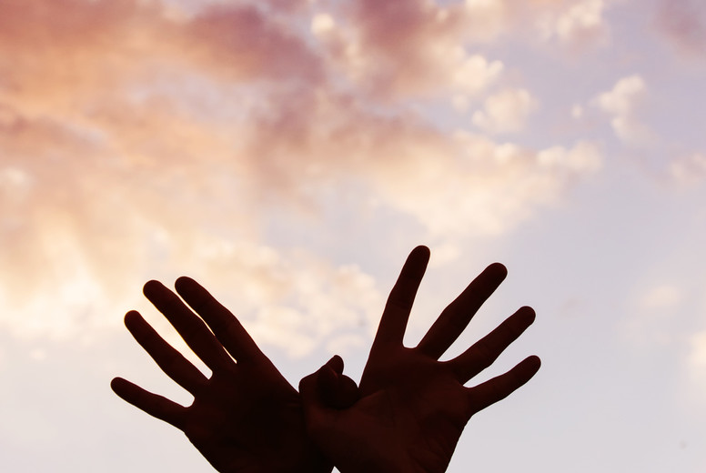 Hands against sky
