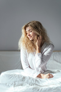 young beautiful girl sitting on a bed