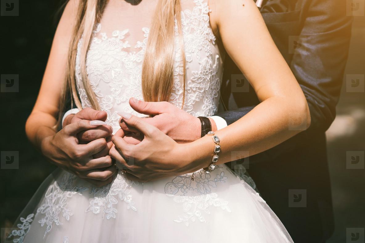 The bridegroom embraces the bride