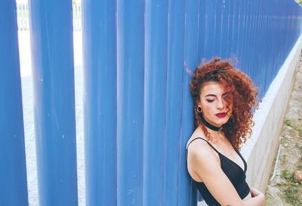 Redhead woman against blue wall