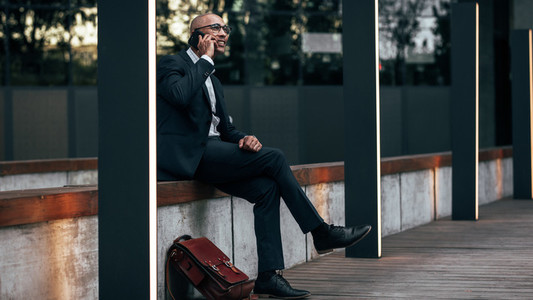 Businessman sitting outdoors talking over mobile phone