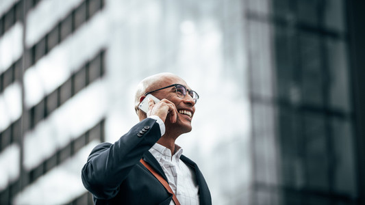 Business executive talking on mobile phone outdoors
