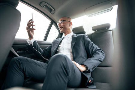 Businessman sitting in car looking at his mobile phone