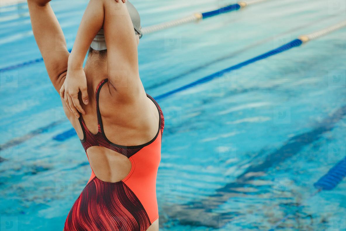 Female swimmer stretching body before swim