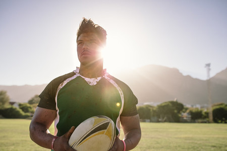 Sportsman holding a rugby ball on field