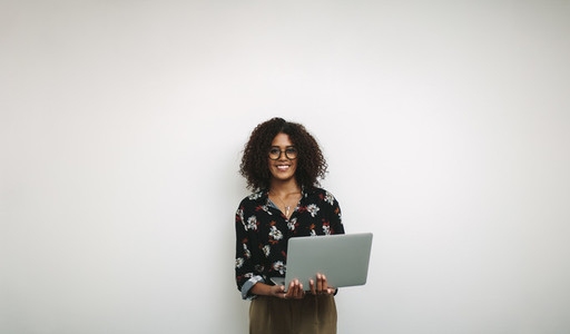 Portrait of a smiling businesswoman in office holding a laptop