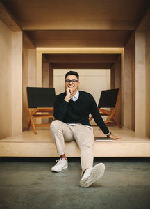 Smiling businessman sitting in office inside an enclosure