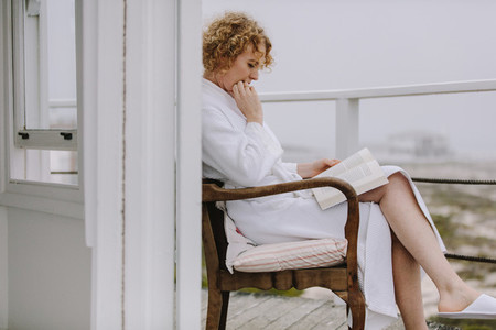 Woman reading a book sitting in balcony