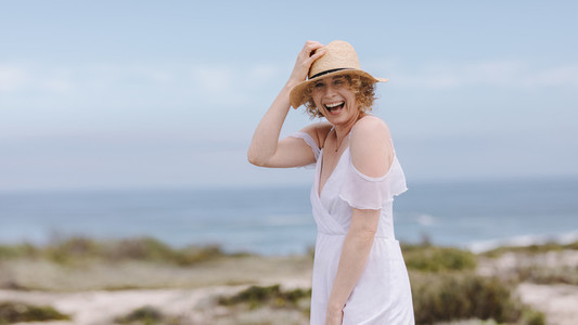 Portrait of a woman standing near sea wearing a hat