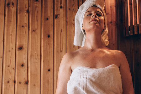 Woman sitting in a wooden spa with eyes closed