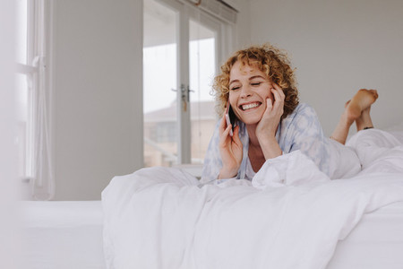 Happy woman lying on bed talking over cell phone
