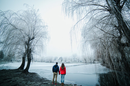 beautiful couple posing near a frozen river