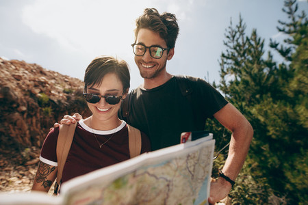 Couple holding a map to find the route to their destination
