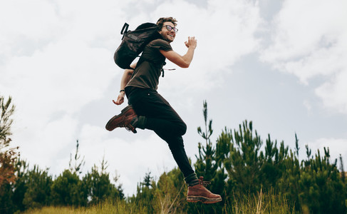 Happy man jumping during his walk in the forest