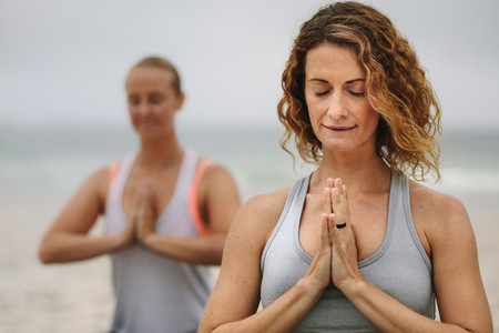 Women practicing yoga at the beach