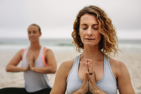 Women practicing meditation and yoga at a beach