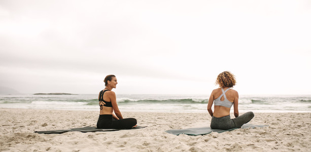 Two women doing yoga sitting at the beach