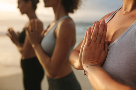 Fitness women practicing yoga standing at the beach