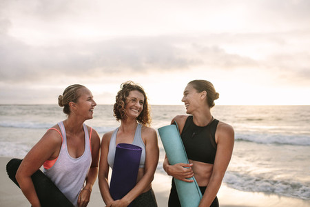 Three women carrying yoga mats standing at the beach