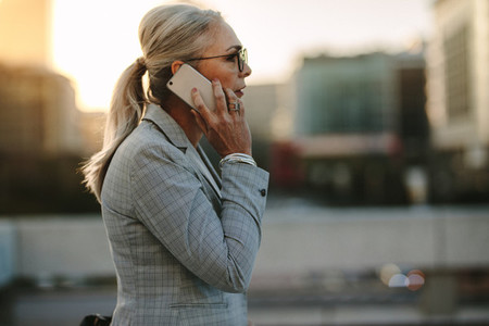 Senior businesswoman talking on cellphone in the city