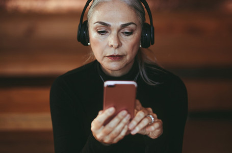 Senior businesswoman listening music from smart phone